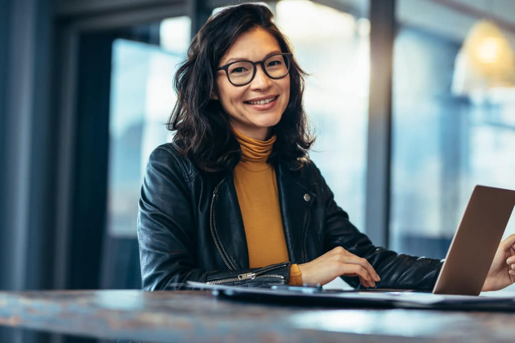 Portrait of attractive business woman sitting at her desk with laptop computer in office. Smiling business woman in casuals at office.
